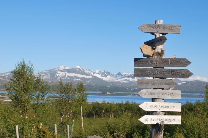 Et treskilt viser vei til noen av de mange turmulighetene i Tydal og Sylan. I bakgrunnen ruver Sylmassivet. Foto: Mattias Jansson
