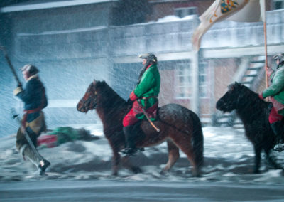Offiserer til hest i snøstorm